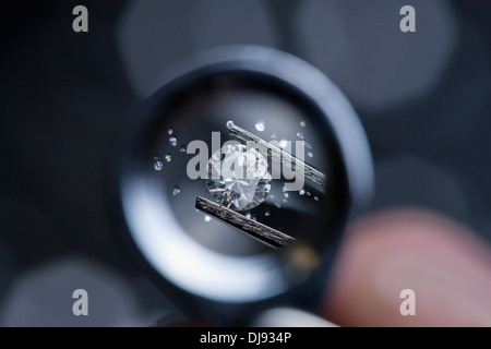 A gemstone being examined through a magnifying loupe. - Stock Photo