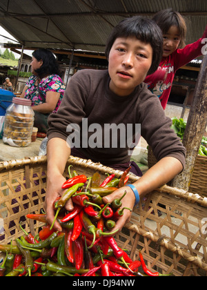 Bhutan, Nobding, woman holding handful of hot red and green chillies in market - Stock Photo