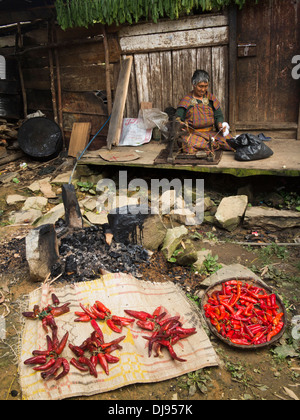 Bhutan, Nobding, woman spinning yak hair whilst waiting to sell red chillies in market - Stock Photo