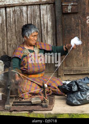 Bhutan, Nobding bazaar, woman spinning yak hair by hand on wheel - Stock Photo
