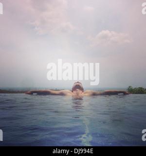 Man relaxing in infinity pool - Stock Photo