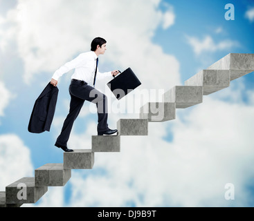 Young businessman climbing grey stairs - Stock Photo