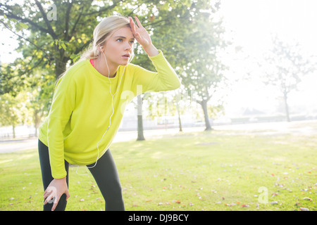 Active exhausted blonde pausing after running - Stock Photo