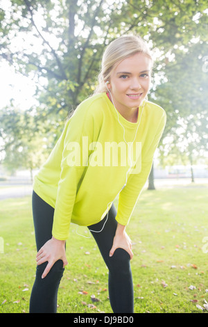 Active smiling blonde pausing after a run - Stock Photo