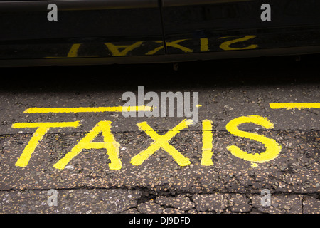 A yellow painted 'Taxi's' sign on tarmac is reflected on the door of a London Black Cab. - Stock Photo
