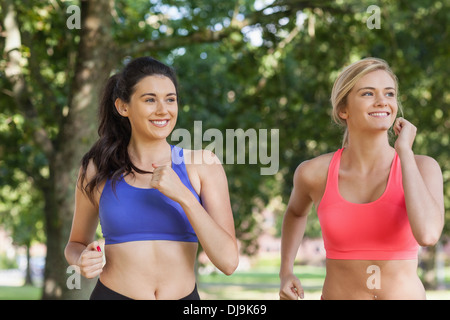 Two sporty women jogging in a park - Stock Photo