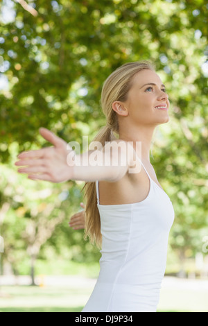 Side view of cheerful attractive woman doing yoga spreading her arms - Stock Photo