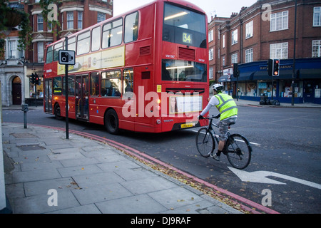 Cyclist cycling on road at side of double decker bus in London - Stock Photo
