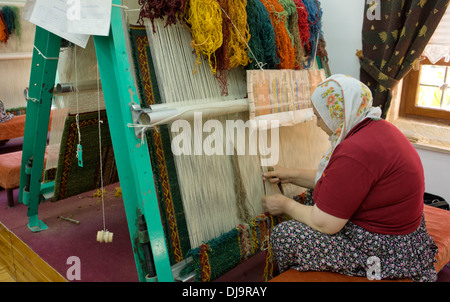 Woman working threading weaving on a loom for a carpet in Turkey - Stock Photo