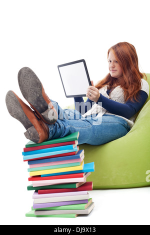Freckled girl using tablet computer at home instead of reading - Stock Photo