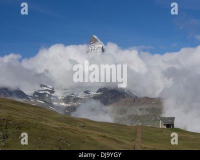 Matterhorn peak emerging from clouds,chapel and footpath at Riffelberg near Zermatt Switzerland in the high Swiss - Stock Photo