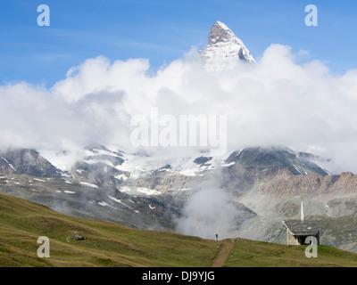 Matterhorn peak emerging from clouds, lone walker on footpath at Riffelberg near Zermatt Switzerland in the high - Stock Photo