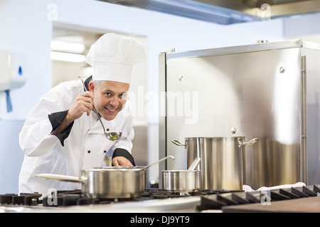 Smiling head chef tasting food from ladle - Stock Photo