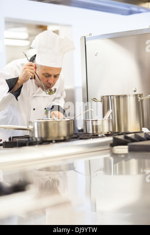 Concentrating head chef tasting food from ladle - Stock Photo