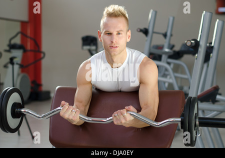 Handsome young man training biceps lifting barbell on bench in a gym. - Stock Photo