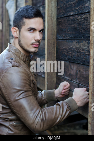 Handsome young man pressing fists on wood planks wall and looking at camera - Stock Photo
