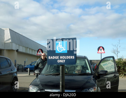 A car parked in a blue badge parking zone for disabled drivers - Stock Photo