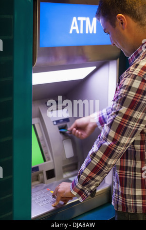 Brunette student withdrawing cash - Stock Photo