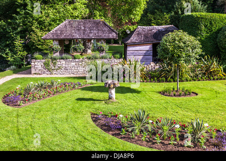 The pretty landscaped garden of the Swan Hotel in the Cotswold village of Bibury in the Coln Valley. - Stock Photo