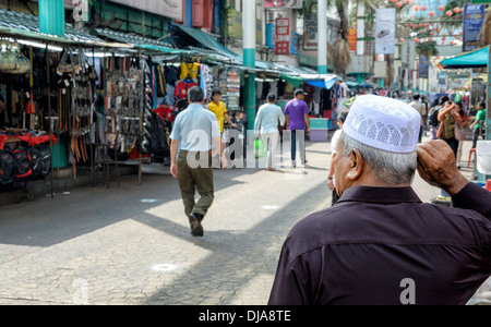 Religious man wearing Islamic hat watches passers-by in a market area / shopping street - Stock Photo