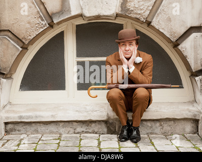 Dapper city gent in a brown suit and matching bowler hat sitting by an arched window with his head in his hands. - Stock Photo