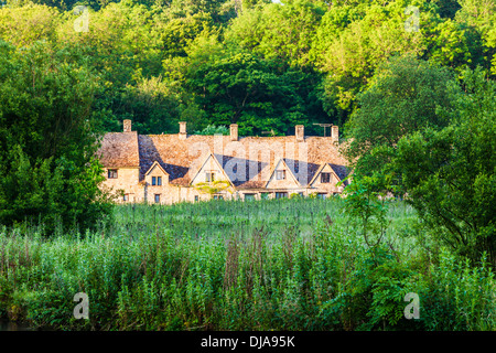View over the Rack Isle water meadow to the famous Arlington Row cottages in the Cotswold village of Bibury. - Stock Photo