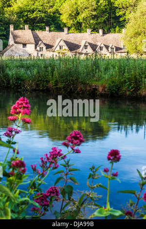View over the River Coln and the Rack Isle water meadow to the famous Arlington Row cottages in the Cotswold village - Stock Photo