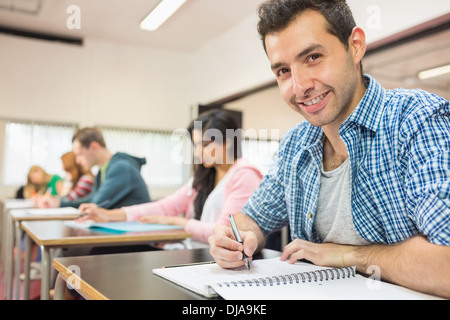Smiling male student with others writing notes in classroom - Stock Photo