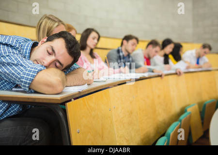 Male sleeping with students in lecture hall - Stock Photo