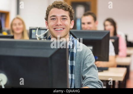 Smiling male student with others in computer room - Stock Photo