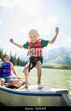 Caucasian boy standing on canoe on lake - Stock Photo