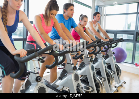 Determined people working out at spinning class - Stock Photo