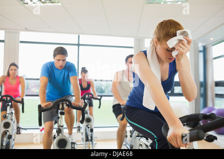 Tired people working out at spinning class - Stock Photo