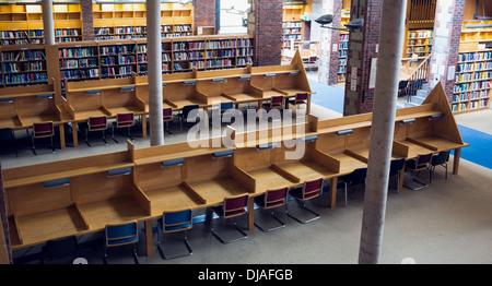 Empty seats and bookshelves at college library - Stock Photo