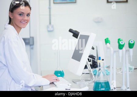 Young female researcher using computer in lab - Stock Photo