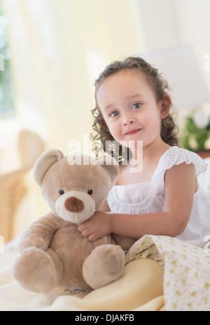 Mixed race girl holding teddy bear - Stock Photo