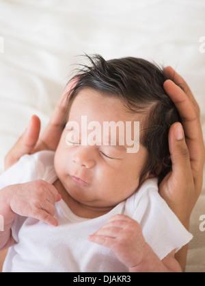 Hispanic mother cradling baby - Stock Photo