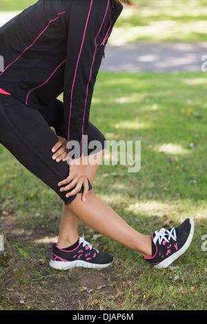 Mid section of woman stretching her leg during exercise at park - Stock Photo