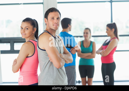 Fit couple with friends standing in background in exercise room - Stock Photo