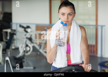 Woman drinking water while working out at spinning class - Stock Photo