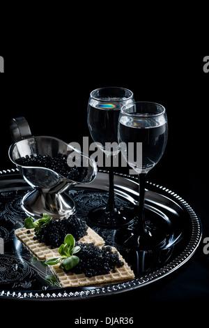 Vodka and black caviar on black background - Stock Photo