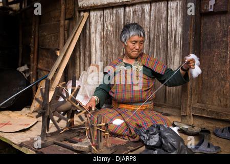 Bhutan, Nobding bazaar, woman spinning cotton thread by hand on wheel - Stock Photo