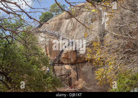 Locals and tourists climbing the stairs at Lion's rock at Sigiriya in Sri Lanka - Stock Photo