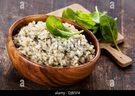 Risotto with spinach in wooden bowl - Stock Photo