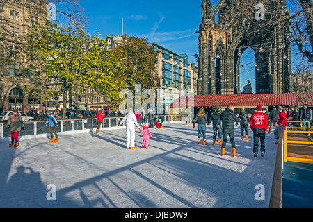 Edinburgh's Christmas in East Princes Street Gardens with ice rink and skaters with Scott Monument behind