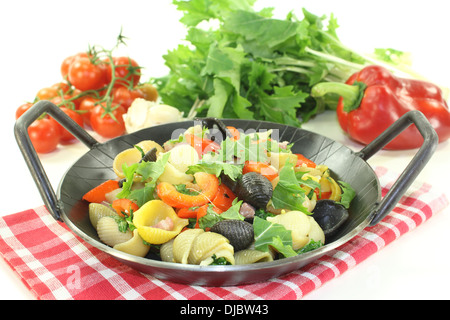 Pasta pan with bell pepper and turnip greens on a light background - Stock Photo