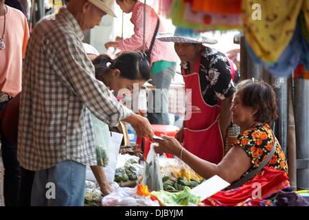 street market stall with customers in Korat, Thailand - Stock Photo