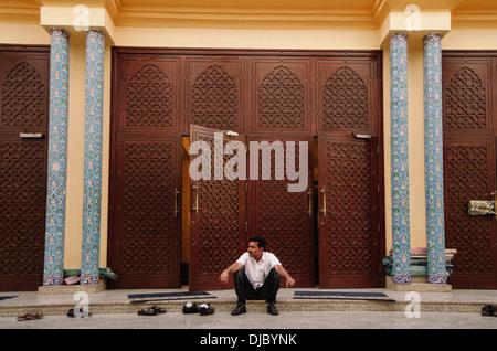 Man sitting on the steps outside the Ali bin Abi Talib Mosque in Bur Dubai. Dubai (United Arab Emirates). - Stock Photo