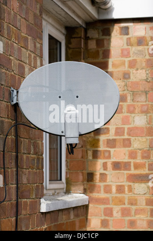 TV satellite dish attached to the side of a UK house. - Stock Photo