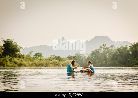 Some local kids enjoying their food on some rocks in the middle of the Nam Song River, Vang Vieng, Vientiane, Laos. - Stock Photo